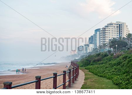 DURBAN SOUTH AFRICA - MAY 24 2016: Locals and tourists on the beach and walking along the promenade in Umhlanga Rocks at Sunset