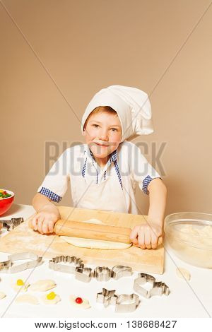 Portrait of kid boy in baker's apron and toque, flattening dough with wooden rolling pin for candy filled cookies, background with copy-space