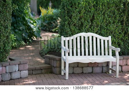 A whitewashed bench sits near a brick walkway that gradually disappears in soft focus.