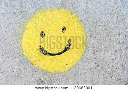 Yellow smiling face (smiley) painted on a sidewalk