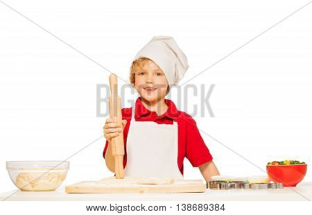 Kid boy in apron and toque baking cookies, holding wooden rolling pin, isolated on white