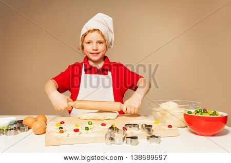 Kid boy in baker's uniform rolling out the pastry for candy filled cookies, standing against the wall with copy-space