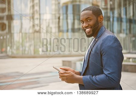 Cheerful african businessman is using mobile phone. He is looking at camera and smiling. Worker is standing outdoors near office