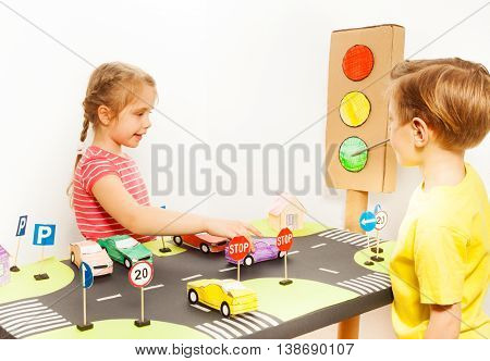 Little girl driving toy car on road playing field, while her friend pointing to the green signal of the handmade light with a pointer in road safety class