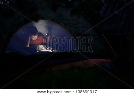 child reading at night in a tent. boy reads a book in the tent by the light of a mobile phone. selective focus