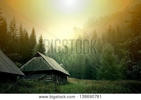 Wooden abandoned house in dark foggy mountains. Fantasy and colorfull nature landscape. Nature conceptual image.