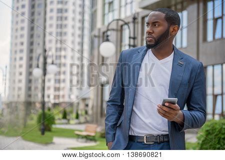 Confident African businessman is waiting for meeting in city. He is standing and looking aside with seriousness. Man is holding smartphone