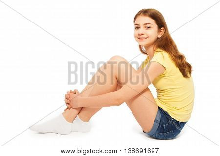 Side view of teenage girl in denim shorts and yellow t-shirt, sitting on the floor, isolated on white background