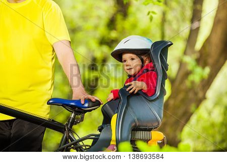 Portrait of little girl in bicycle helmet sitting in bike child seat during cycling in sunny forest