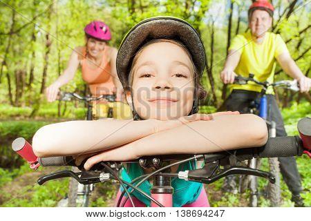 Portrait of happy smiling girl in bicycle helmet, bracing against handlebar of the bike
