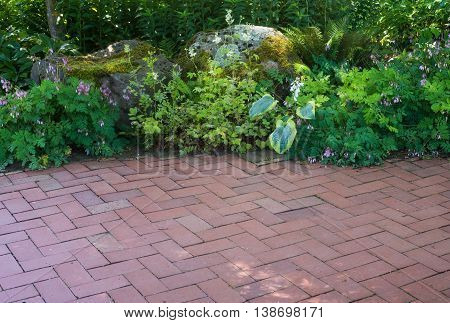 A natural shade perennial garden borders a brick patio