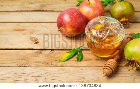 Jewish holiday Rosh Hashana background with honey jar apple and pomegranate on wooden table