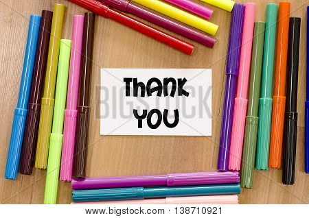 Thank you written on memo over wooden background