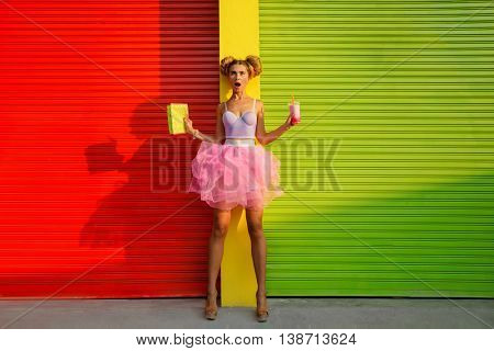 Girl drinking milk against red urban wall background.