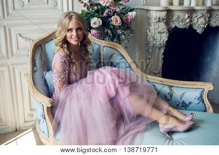 young sexy blonde girl sitting on the couch in Lacy pink dress turns her head and smiles portrait