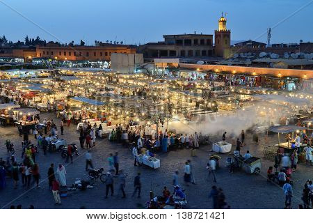MARRAKESH - JULY 09: Unidentified people visit the Jemaa el Fna Square at sunset, July 09, 2013 in a Marrakesh, Morocco. The square is part of the UNESCO World Heritage.