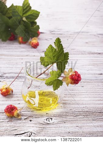 A small glass jar with a rare northern cloudberry oil with berries and leaves on the gray wooden structural background. The concept of the use of rare natural oils useful plant