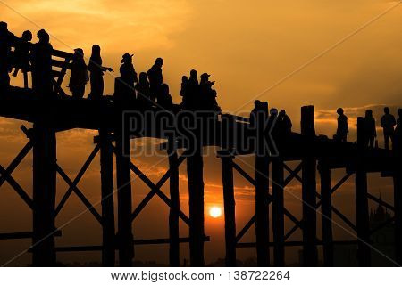 Silhouetted people crossing U bein bridge with sunsetThe longest wooden bridge in MandalayMyanmar.