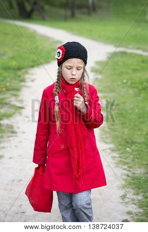girl walking by winding pathway with dandelion flower in hand