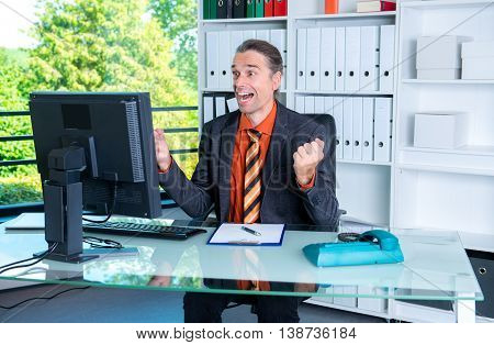 Young Amazed Business Man At His Desk