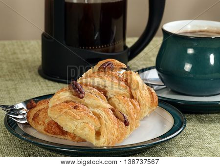 maple syrup and pecan danish pastry with coffee