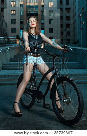 Woman biker in night city sits on a bicycle.