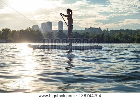 Sup Silhouette Of Young Girl Paddle Boarding At Sunset11