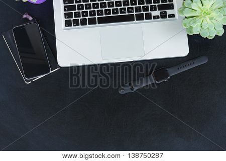 Laptop, watch and phone on black table mack up flat lay scene, copy space on black table