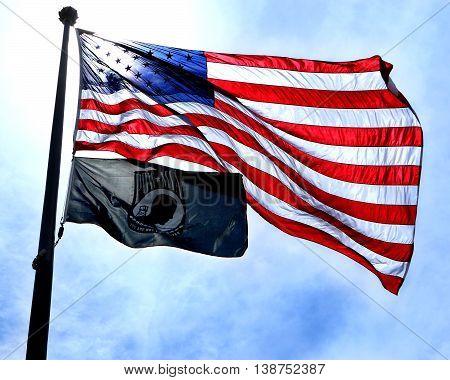 American flag and MIA flag against blue sky