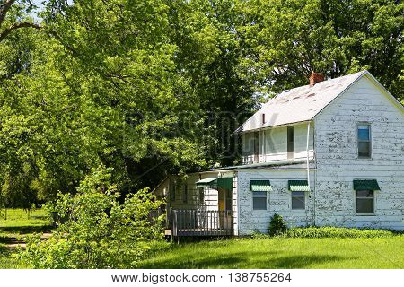 HALSTEAD, KANSAS, USA - MAY 17, 2015: An abandoned house with big trees around it near Halstead.