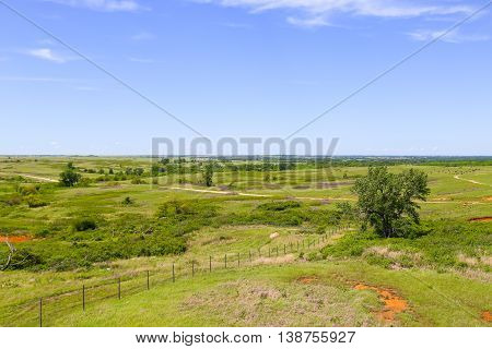 CANTON, KANSAS, USA - MAY 17, 2015: Overlook of the Maxwell Wildlife Refuge near Canton with rolling hills and some trees in the back a buffalo herd is grazing.