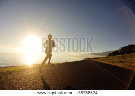 healthy lifestyle young woman runner running on sunrise seaside road