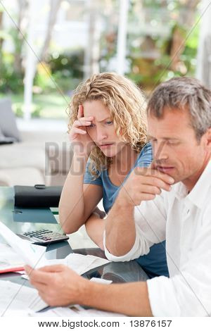 Desperate couple calculating their domestic bills at home
