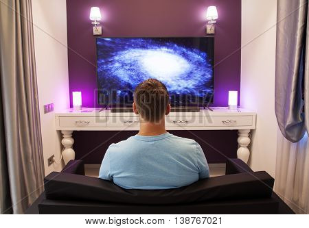 Man watching 4K TV in the living room view from the back