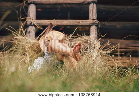 Barefoot boy sleeps on the grass near ladder in haystack