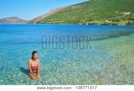 greek girl sitting inside the sea at Ithaca Ionian islands Greece