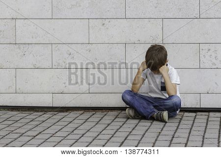 Sad, lonely, unhappy, disappointed, upsed, tired child sitting alone on the ground Outdoor