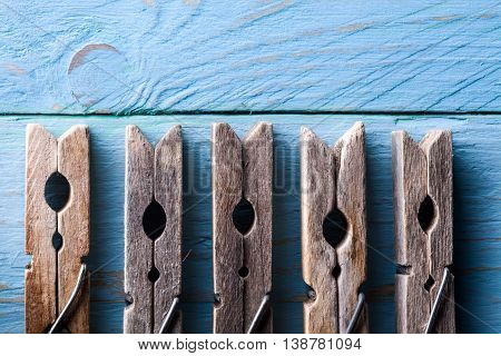 Five Wooden Clothespins Close Up on Blue Wood