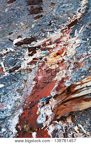 Rusty, dirty stream flowing through the technological waste landfill. Ecological catastrophy.
