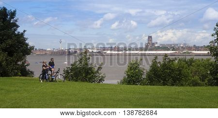 NEW FERRY, ENGLAND, JULY 3. The Wirral Circualr Trail on July 3, 2016, in New Ferry, England. A biking couple pauses to take in the Liverpool skyline on the Wirral Circular Trail passing through New Ferry England.