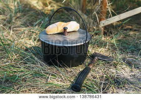 Tourist pot hanging over the fire on a tripod. bread and hatchet next