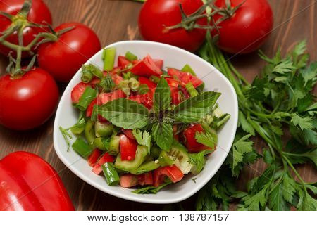 fresh vegetable salad in a white mask on a wooden table