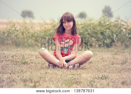 teen girl sitting on the dry grass in the summer