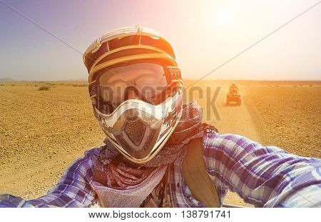 Happy young guy take selfie during desert excursion by quad - Man in helmet and adventure clothes make photo during vacation in exotic scenarios - Concept of activity holiday freedom and adventure