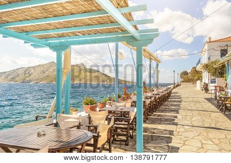 Summer photo with panoramic view from Aegina island in Greece. Beautiful place for making lunch on seafront with wooden roof of bar and restaurant. Magic moment during sunny day for chilling and relax