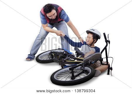 Portrait of little child learn to ride a bike and falling off crying and get help from his father