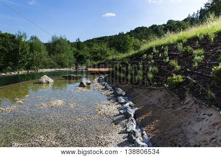 Natural swimming pond purifying water without chemicals through filters and plants poster