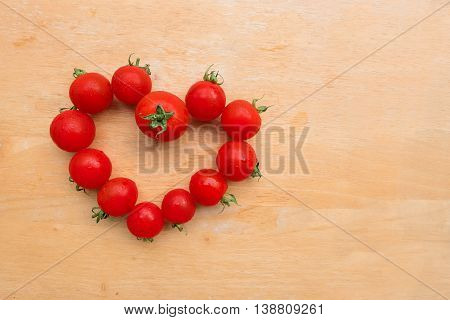 Cherry Tomato fresh in heart shape on wooden chopping board. lycopene and antioxidant in fruit nutrition good for health and skin.