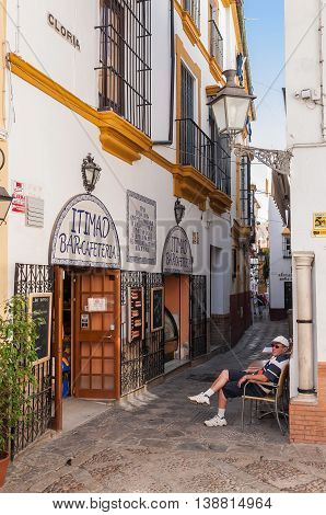 Seville Spain - August 28 2014: Tourist sits in front of the traditional cafeteria on the narrow street of Seville.