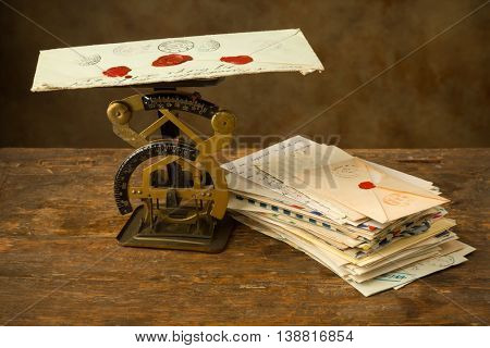 Antique letter scale on an old wooden table with a bundle of letters
